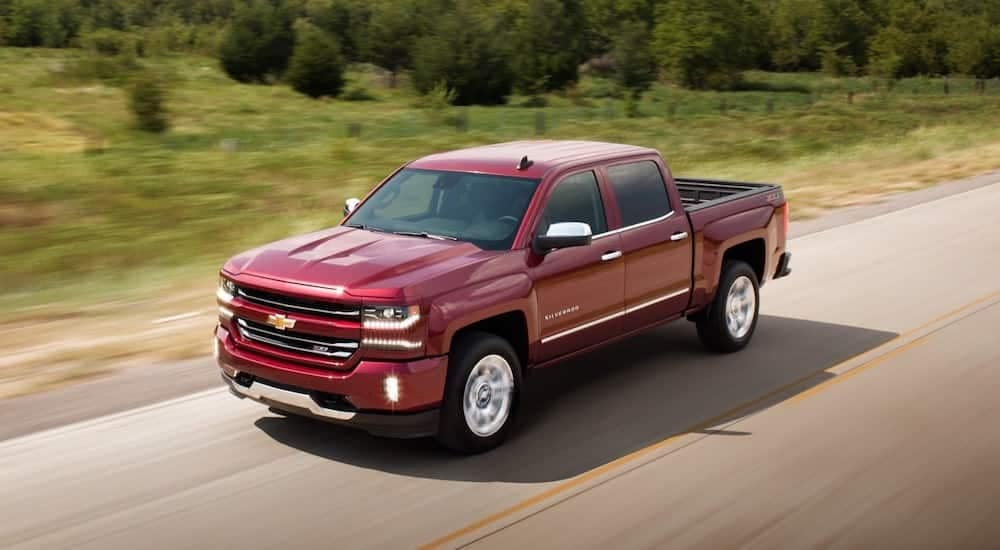 A used red 2017 Chevy Silverado travels an empty road.