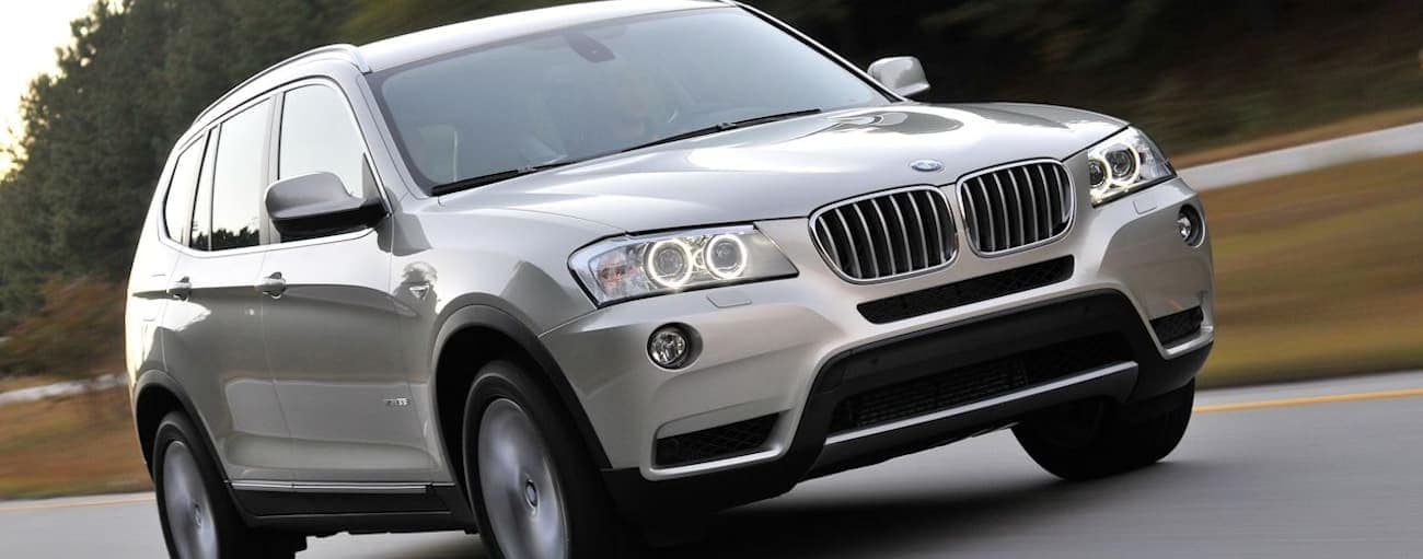 The front of a silver 2011 used BMW X3 driving town a tree-lined road