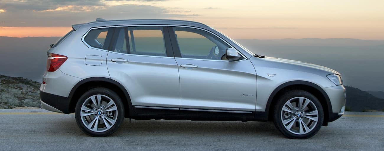 A silver 2012 used BMW X3 parked atop a cliff at sunset with mountains in back