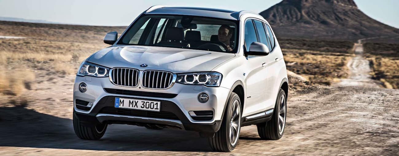 A white 2015 used BMW X3 driving in the desert with mountains in back