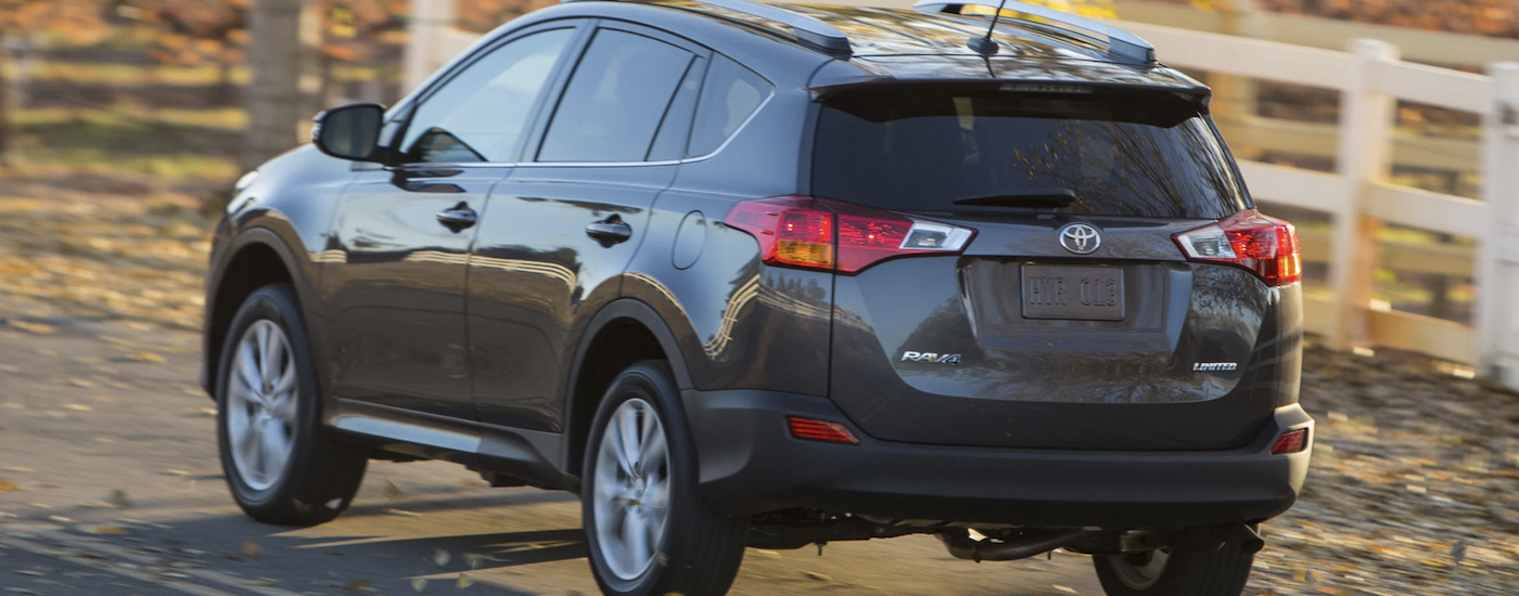 Gray 2013 Used Toyota RAV4 driving by white fence