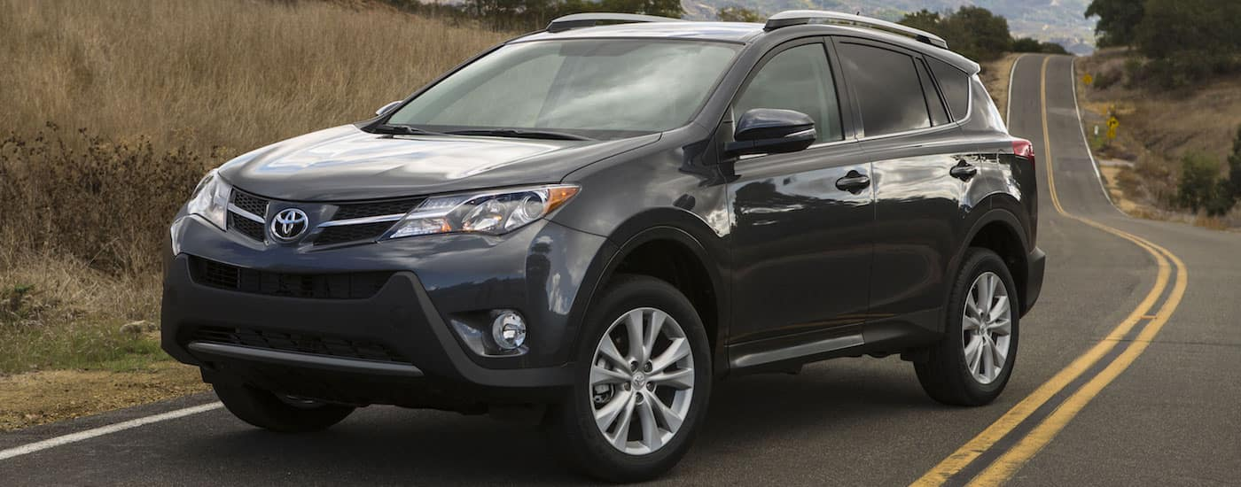 Black 2014 Used Toyota RAV4 driving on hilly road
