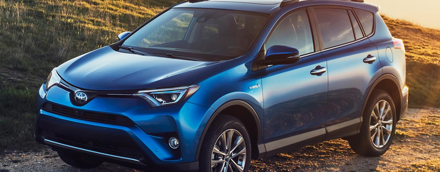 Blue 2016 Used Toyota RAV4 in field at sunset