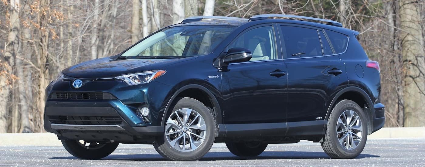 Dark blue 2017 Used Toyota RAV4 parked on wooded street in fall