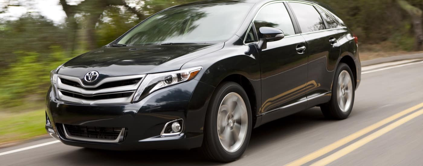 Black 2013 used Toyota Venza driving on tree-lined road