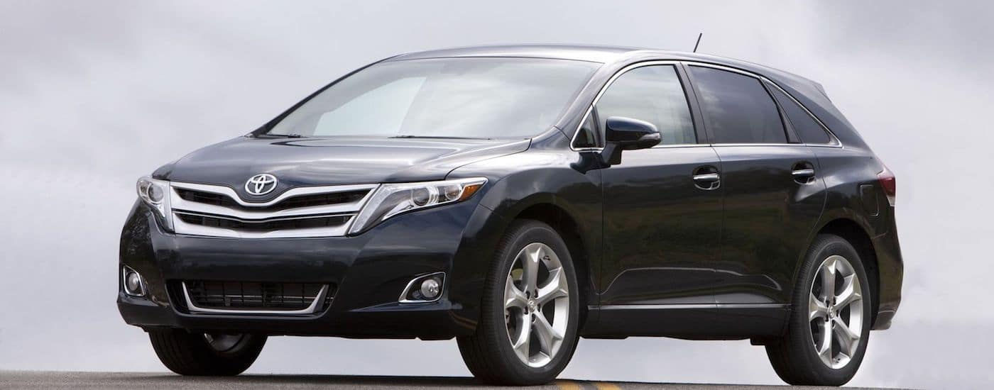 Black 2015 used Toyota Venza against clouds