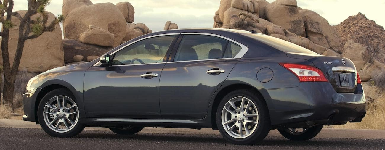 A blue 2009 used Nissan Maxima in front of desert rocks