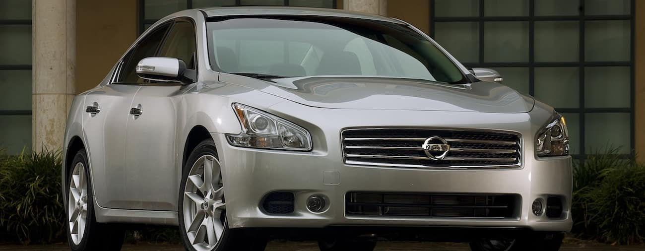 A clean silver 2011 used Nissan Maxima in front of a building with columns