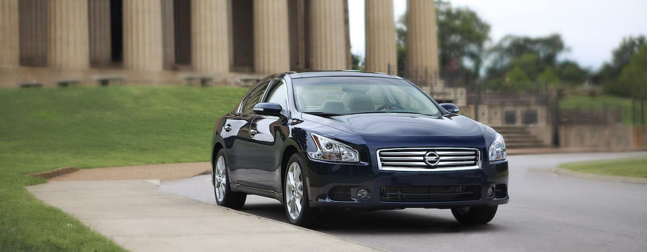 A blue 2012 used Nissan Maxima in front of a public building with columns