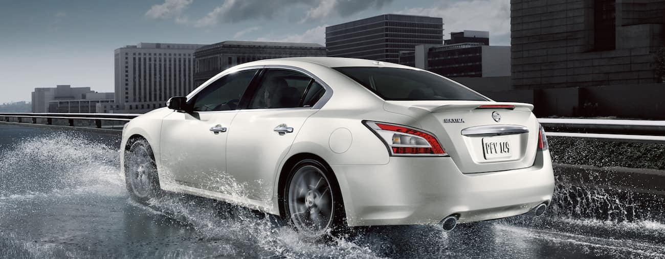 A white 2014 used Nissan Maxima on a rainy highway in a city