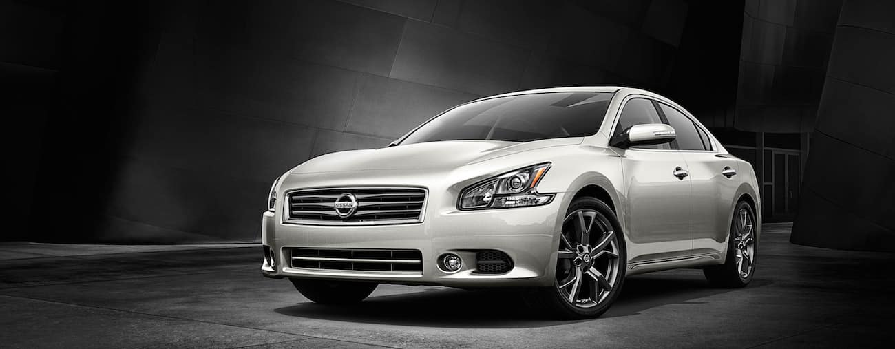 A pearl white 2015 used Nissan Maxima against a black backdrop