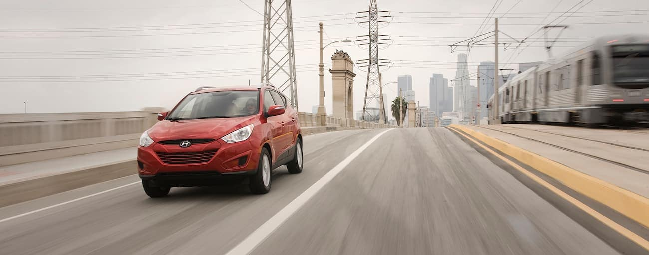 A red 2012 used Hyundai Tucson driving away from a city