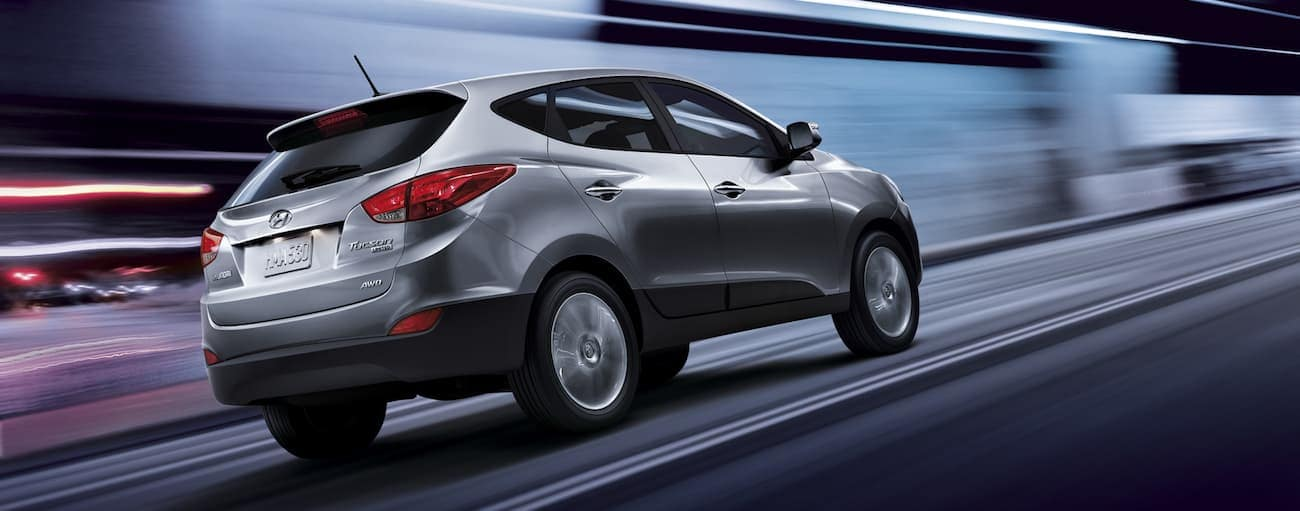 A silver 2013 used Hyundai Tucson races down a city street at night