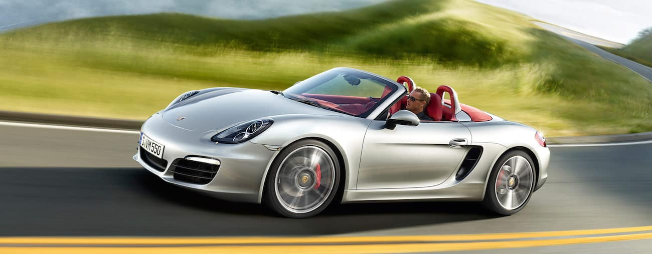 A silver 2012 used Porsche Boxter cruises a grassy hilly road