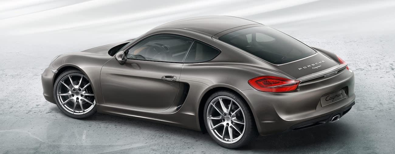 A deep metallic gray 2013 used Porsche Cayman against a light gray backdrop