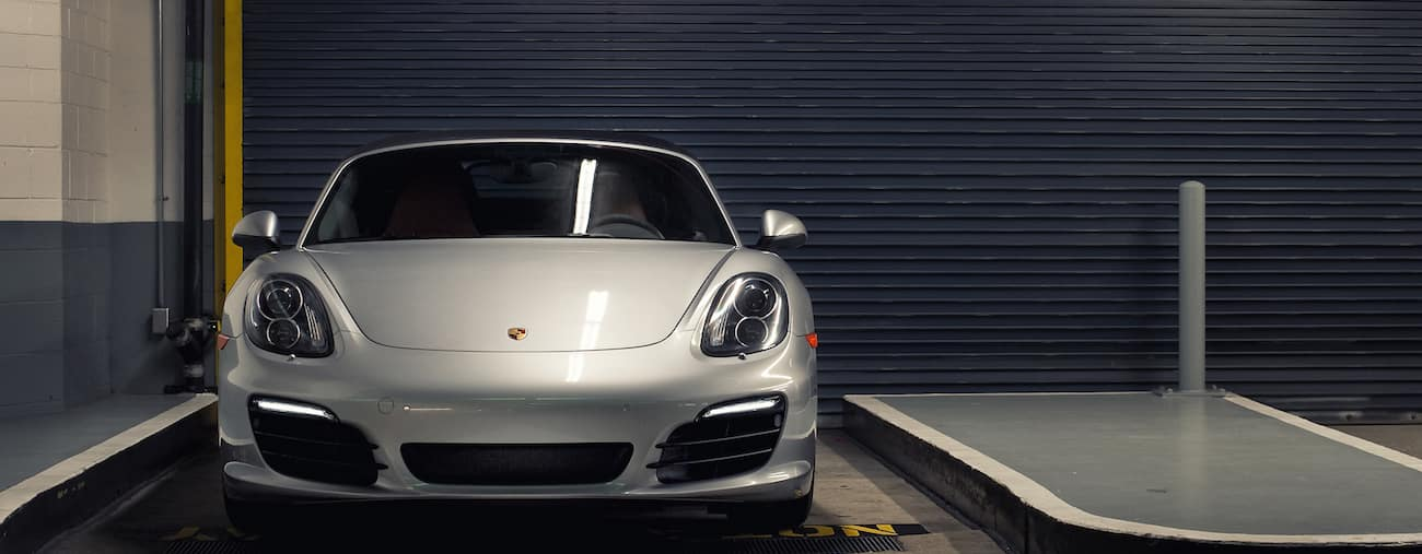 A sleek and stylish white 2014 used Porsche Boxter in a parking garage