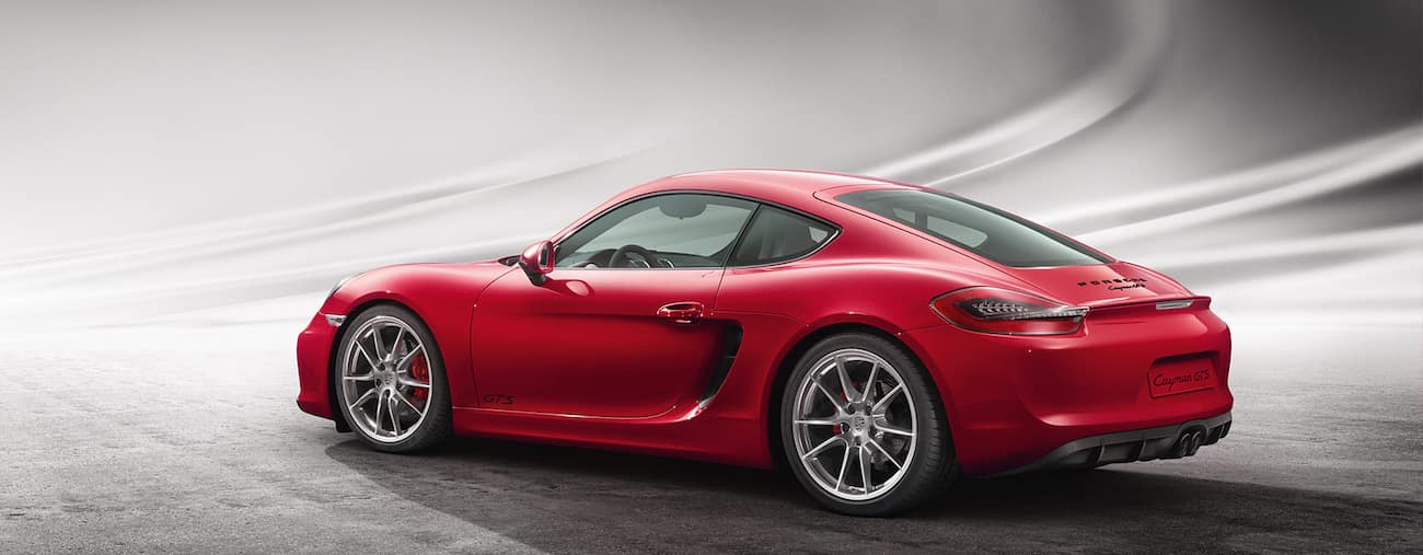 A deep red 2015 used Porsche Cayman on a light background