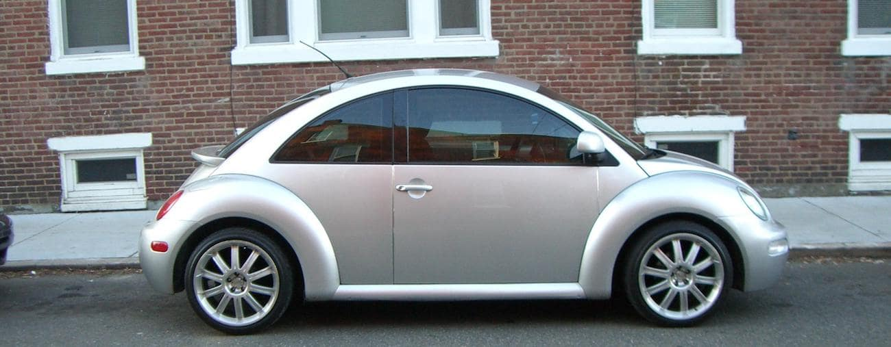 A silver 1998 used Volkswagen Beetle from a local Cincinnati car dealer outside a brick condo building