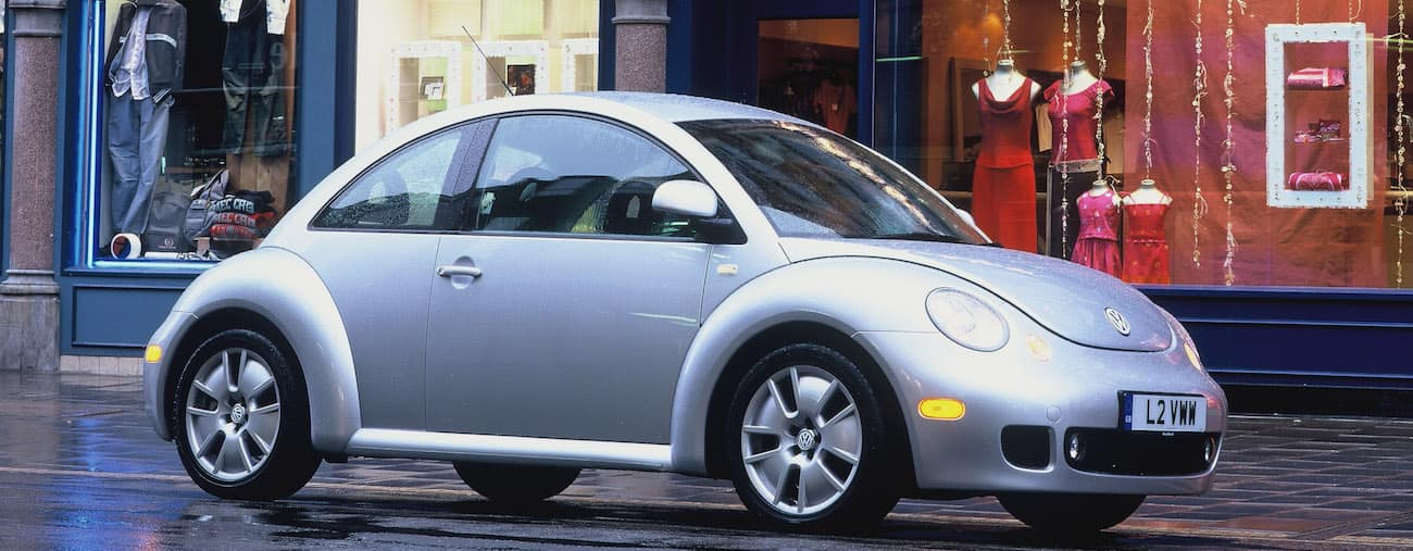 A silver 2005 used Volkswagen Beetle outside a local shop