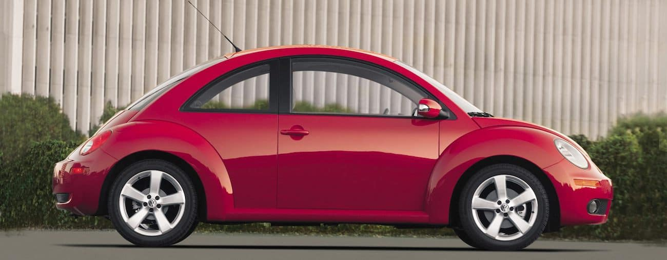 A bright red 2010 used Volkswagen Beetle in front of a brown building with bushes