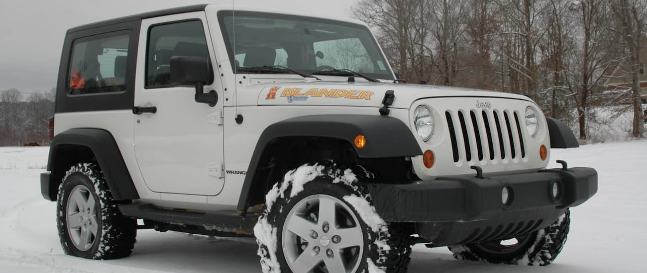 A white 2010 used Jeep Wrangler Islander in the snow