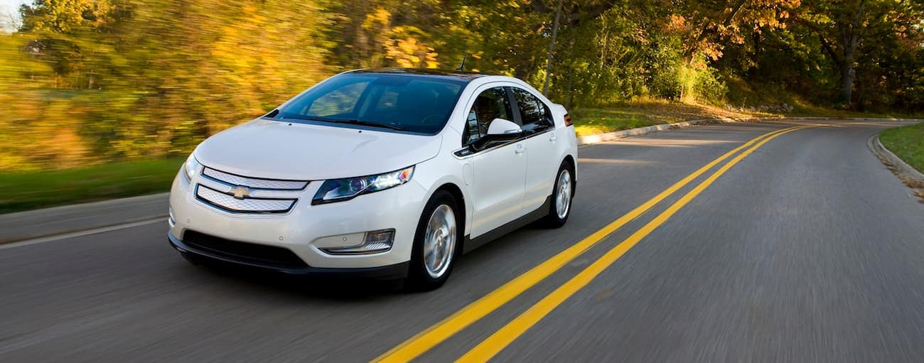 A white 2011 used Chevy Volt driving on a tree-lined road in fall