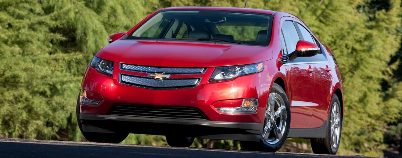 A red 2013 used Chevy Volt driving in front of evergreen trees