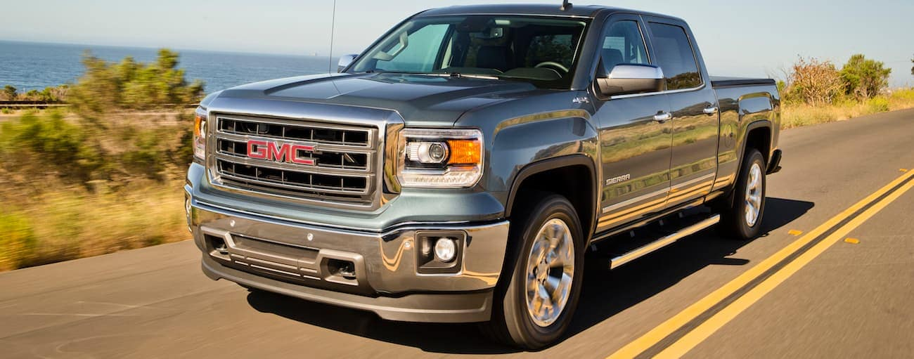 A blue 2014 used GMC Sierra driving along the waterfront