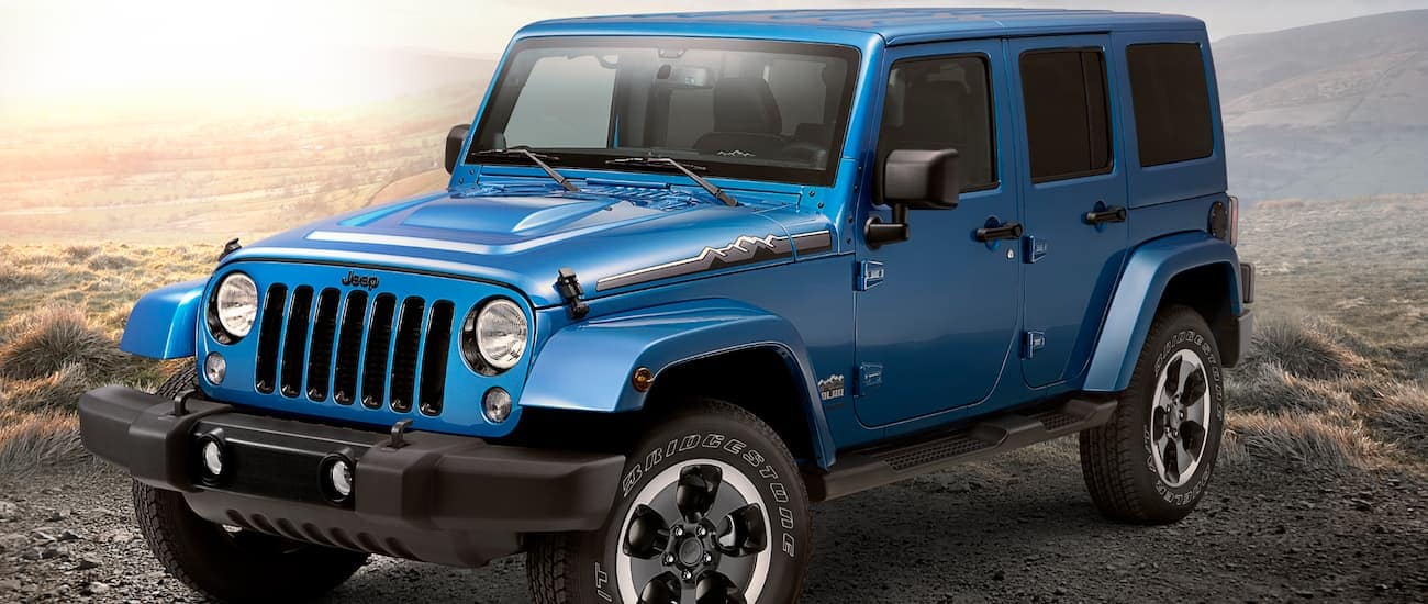 A blue 2014 used Jeep Wrangler on a desert hill at sunset