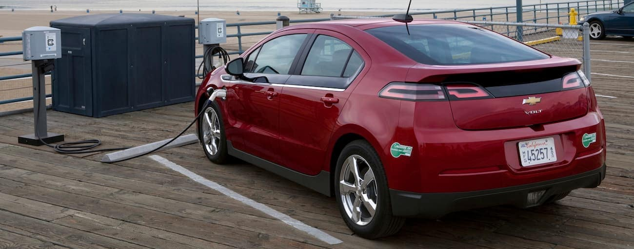 A red 2015 used Chevy Volt charging on a boardwalk