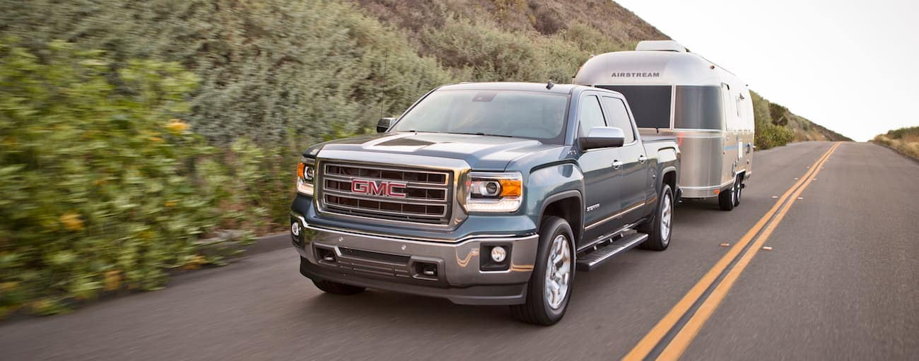 A blue 2015 used GMC Sierra towing an airstream camper