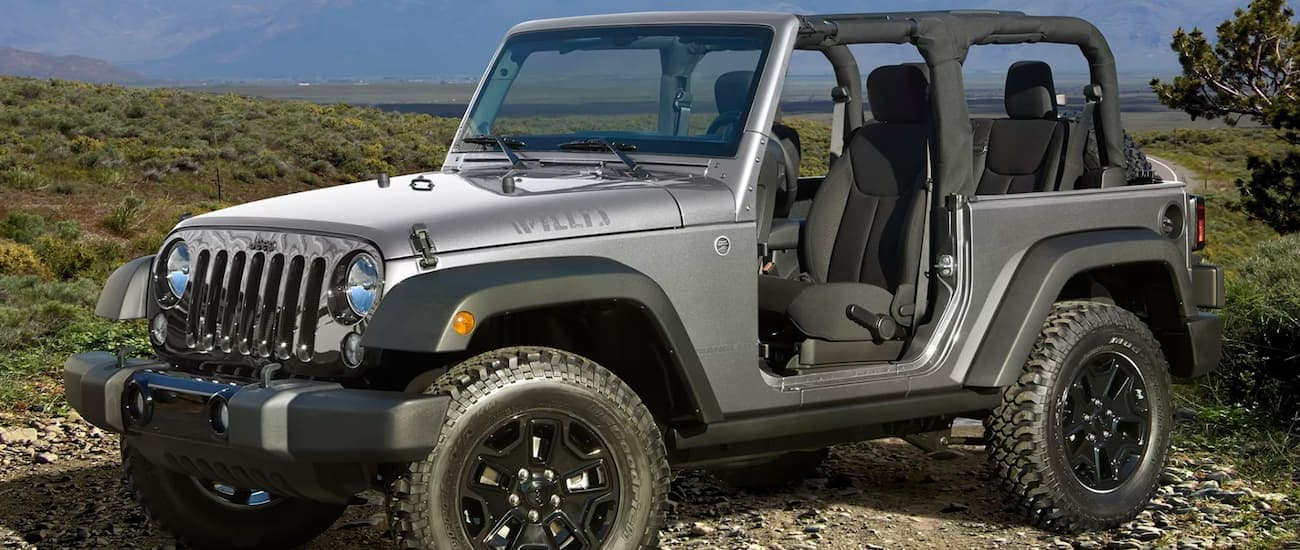 A silver 2016 used Jeep Wrangler Willy on a mountain