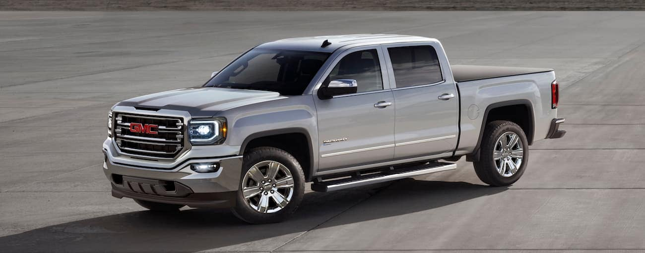 A silver 2017 used GMC Sierra in a large parking lot