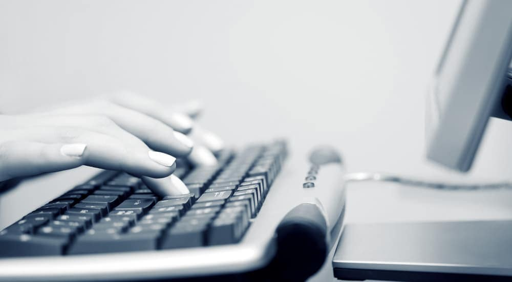 A black and white picture of hands on a keyboard