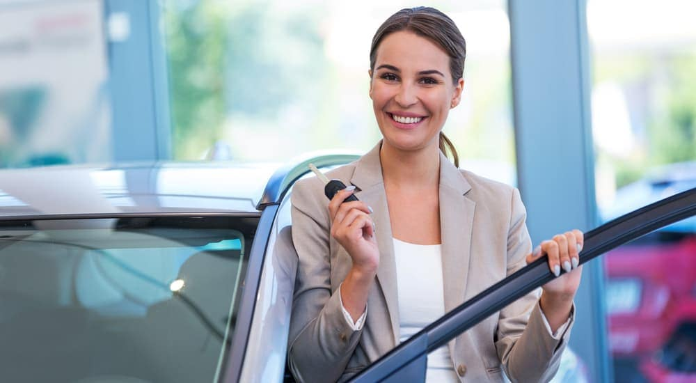 A woman stands inside a dealership with her new car key