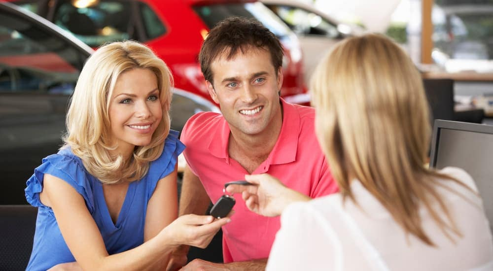 A saleswoman is handing a couple the keys to their new car at a buy here, pay here dealership in Cincinnati, OH.