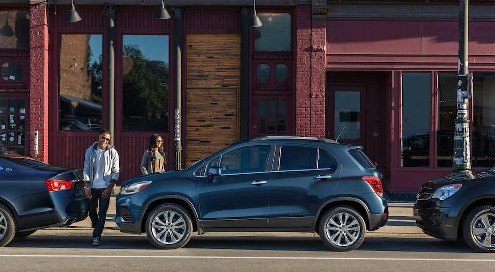 A couple is walking to their 2019 Chevy Trax outside town shops.