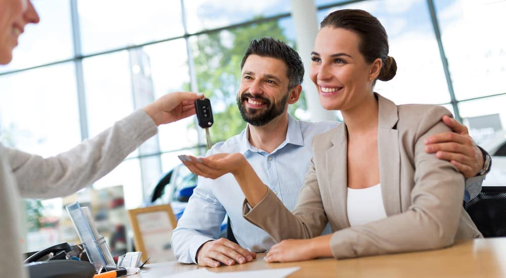 A couple is being handed their new car keys after purchasing at a Buy Here Pay Here dealer in Indianapolis.