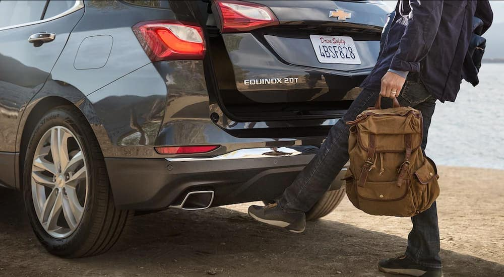 A man is using the lift gate feature on his 2018 Chevy Equinox to load his gear in.