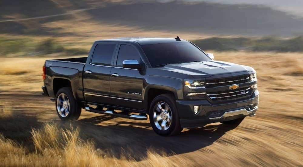 A black 2018 Chevy Silverado is driving on a dirt road with out of focus fields behind it. The Silverado is a common result when searching for Used Cars Dayton, Ohio.
