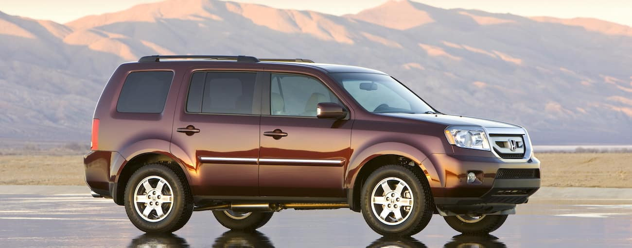 A burgundy 2009 used Honda Pilot is shown with mountains at sunset behind it.