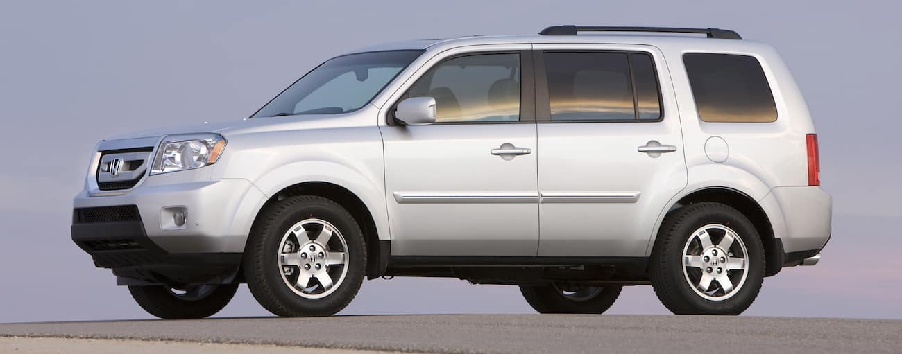 A white 2011 used Honda Pilot against a purple sunset
