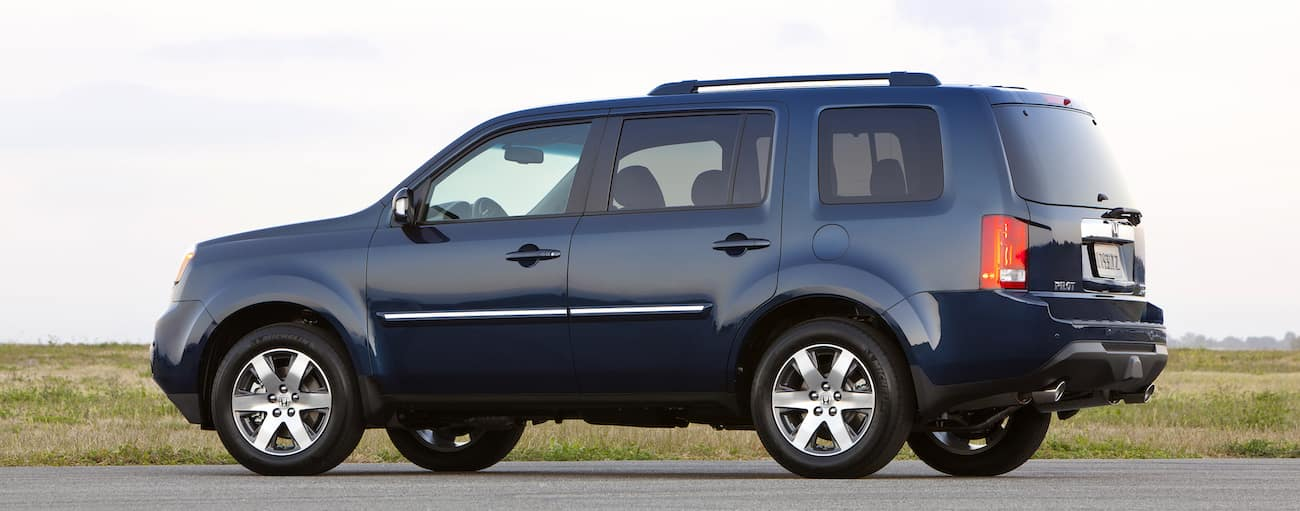 A blue 2012 used Honda Pilot is shown Parked with grass behind it. Check out a used Honda Pilot at a used car dealer.
