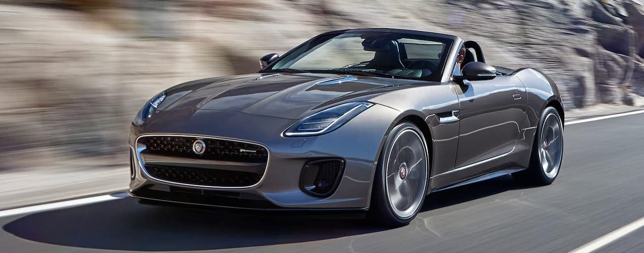 A grey 2018 convertible Jaguar F-Type is driving fast. Check one out a Cincinnati, OH dealership.
