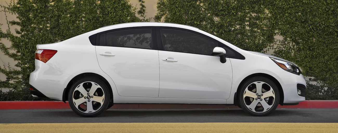 A white 2015 used Kia Rio is parked in front of bushes. Check out a used Kia Rio at a local used car dealer.