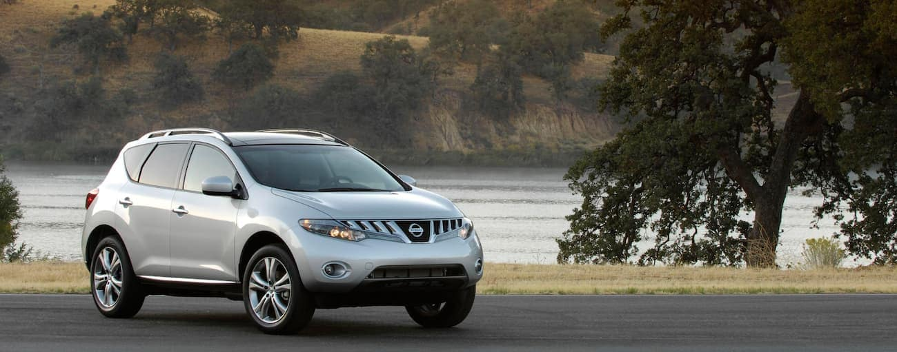 A silver 2009 used Nissan Murano is parked in front of a pond.