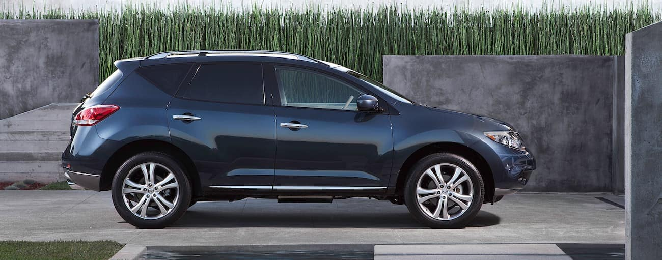 A dark blue 2011 used Nissan Murano is parked in a driveway with tall grass.