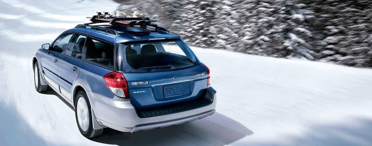 A blue 2009 used Subaru Outback racing through the snow