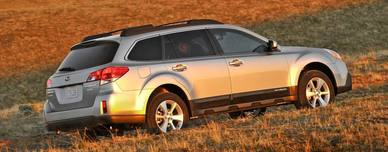 A silver 2014 Used Subaru Outback driving along a grassy hill at sunset