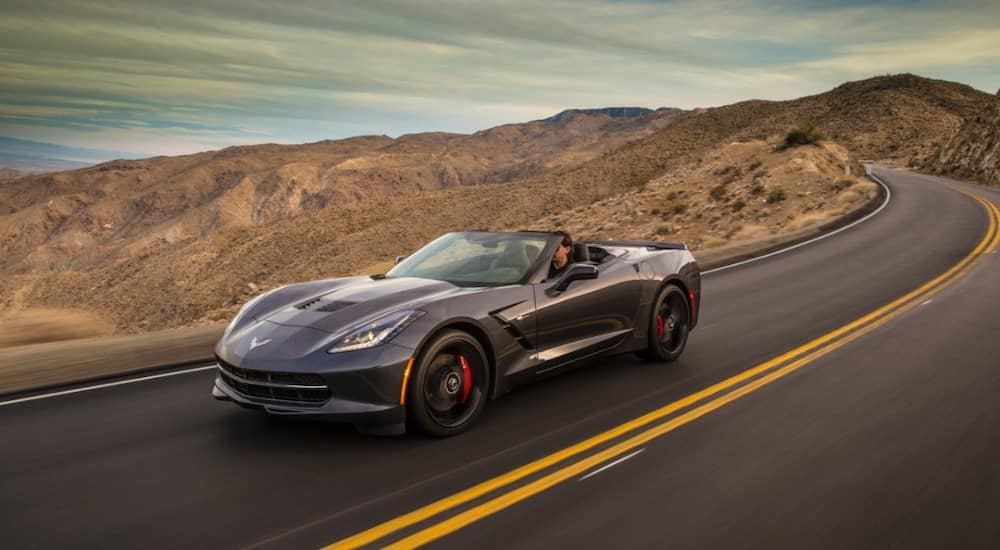 A dark grey 2014 Chevy Corvette is driving through desert mountains. When checking out used cars, Dayton, Ohio is a good place to look.